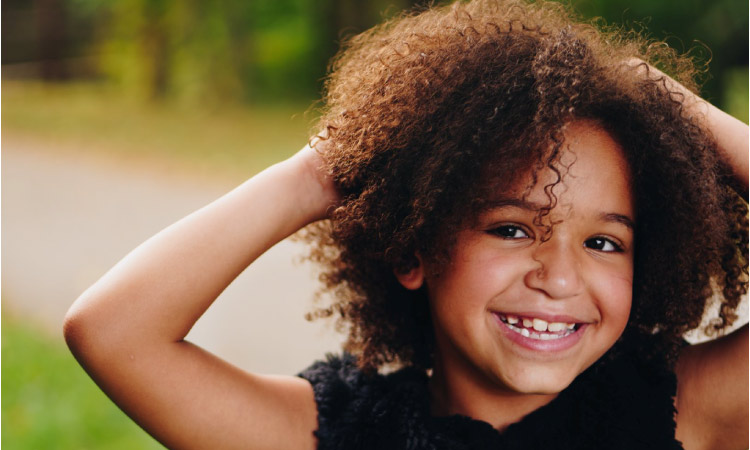 young girl smiling holding her head