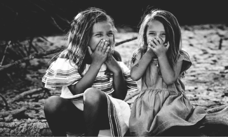 two young girls holding their mouths with dental sealants