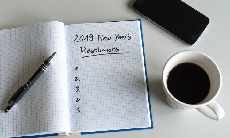 2019 new year resolutions notebook, a pen, cup of coffee and cell phone
