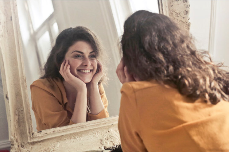 girl smiling into a mirror after teeth whitening treatments