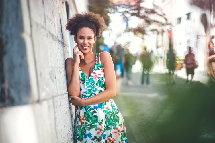 Brunette woman wearing a floral summer dress smiles with a dental bridge while standing against a cement wall