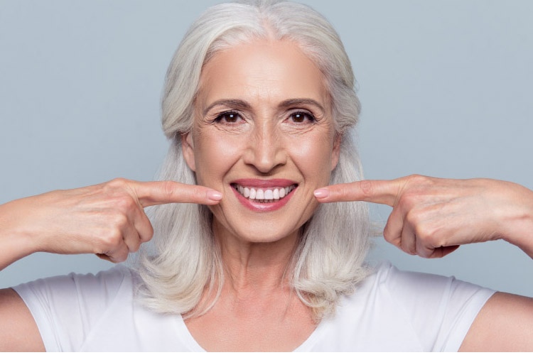 woman with white hair pointing at her teeth whitened smile with both index fingers