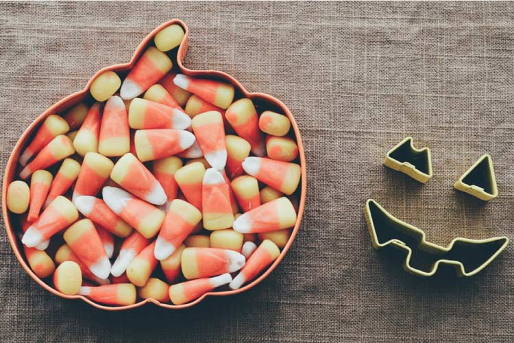 candy corns in a pumpkin shaped bowl