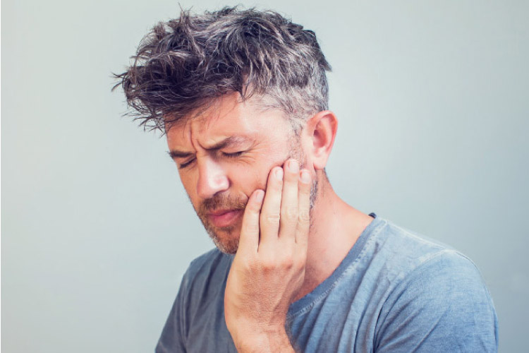man holding his jaw in pain in need of root canal therapy