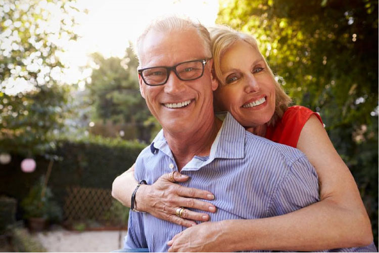 senior couple hug and smile after learning how to care for dentures