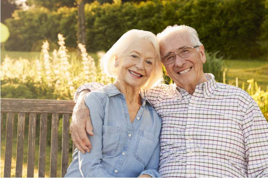 senior couple sitting on a bench hug and smile after improving their smiles with dentures