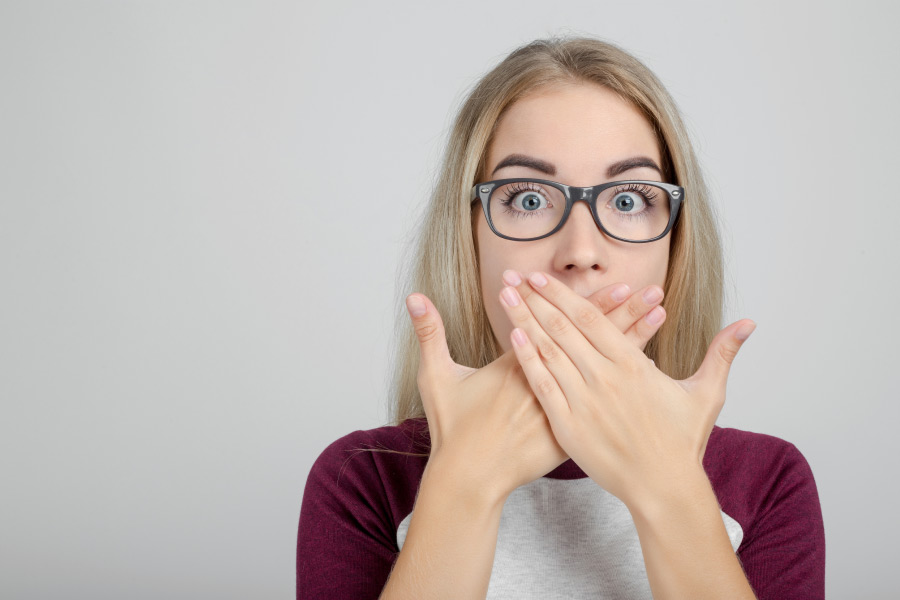 young woman wearing glasses covers her mouth with both hand to hide bleeding gums