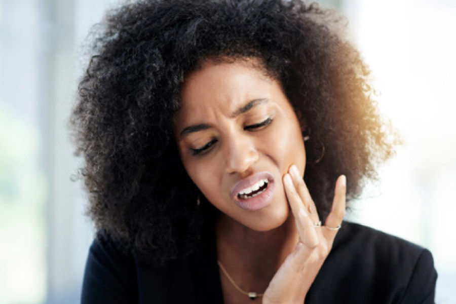 woman holds her jaw in pain with a dental emergency