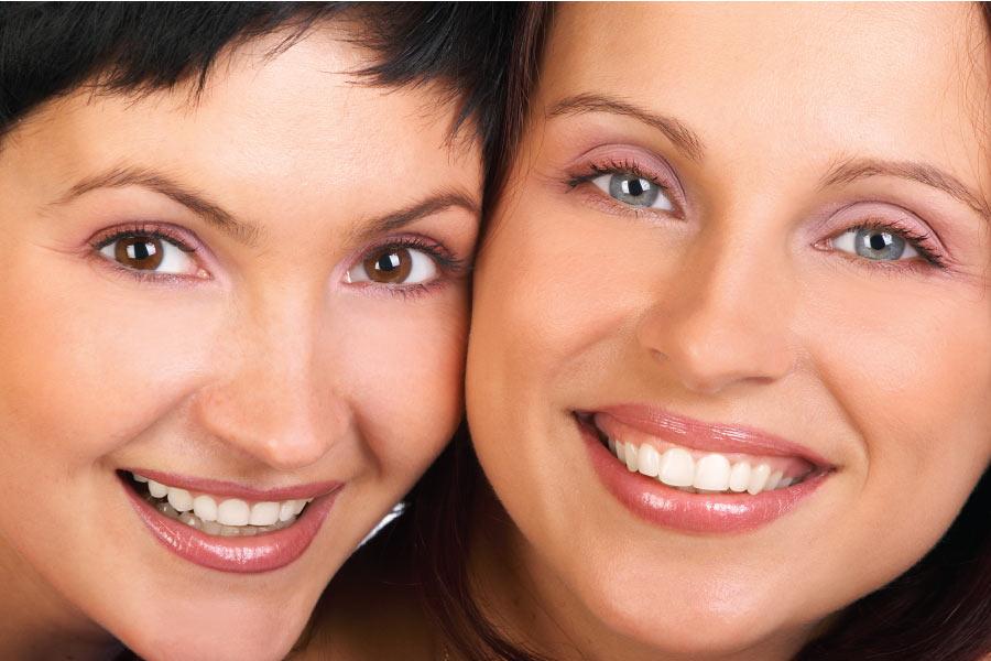 two women smile showing off their veneers